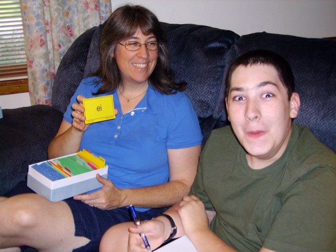 Happy mother reviewing phonogram cards with son