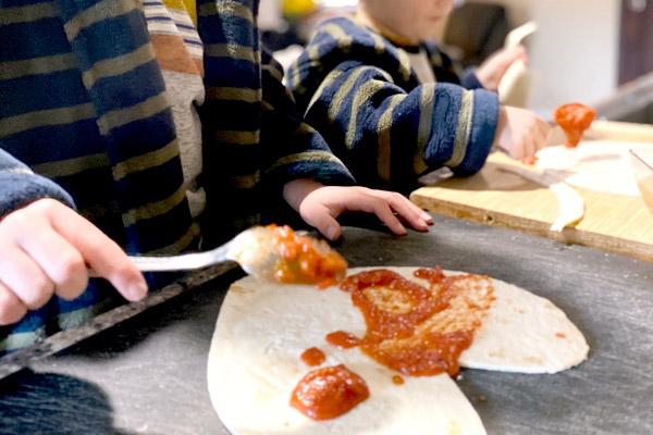 Little boys spreading pizza sauce on tortillas