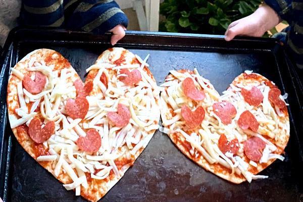 Preschoolers cooking heart-shaped pizza