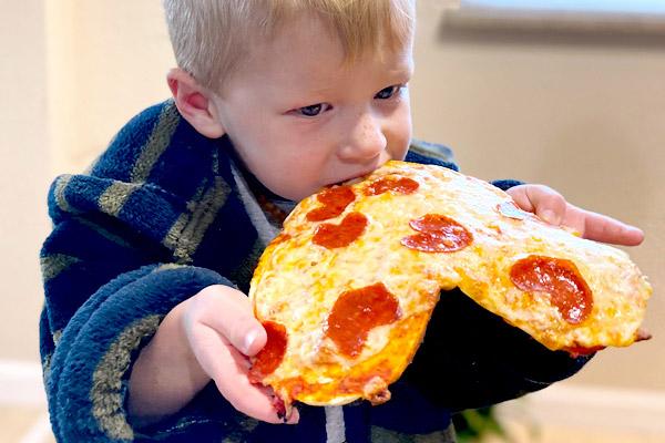 Young boy enjoying Valentine's pizza