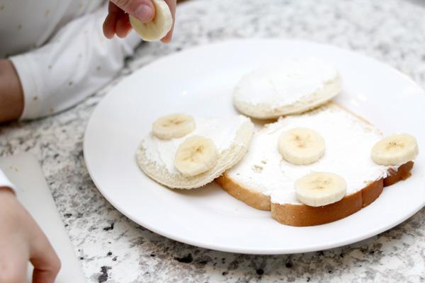Children adding banana slices to bread