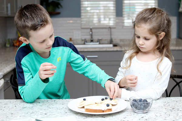 Preschooler and young boy adding blueberries to ABC snack