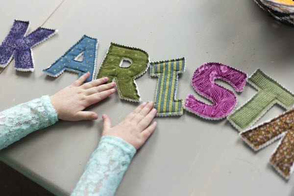 Preschooler spelling out name with fabric alphabet