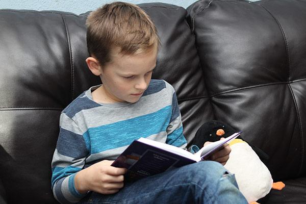 Boy reading on big comfy chair