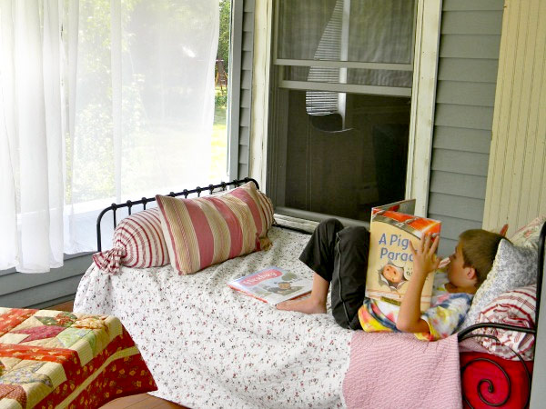 Boy reading in bed on a breezy porch