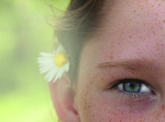 girl's face with flower behind her ear