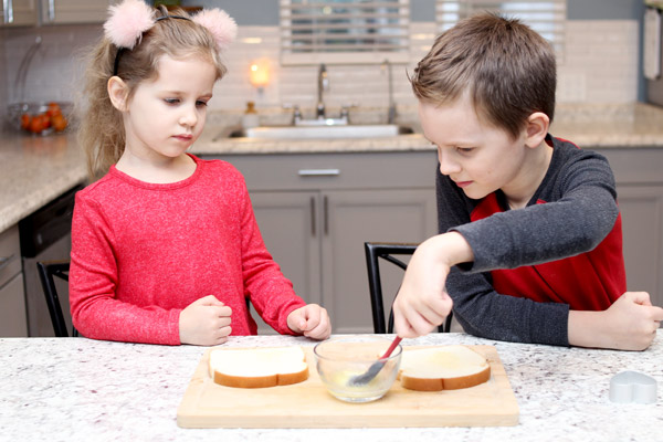 Young boy and girl buttering bread