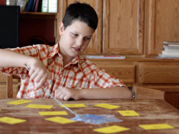 Child using fly swatter game to review phonogram cards
