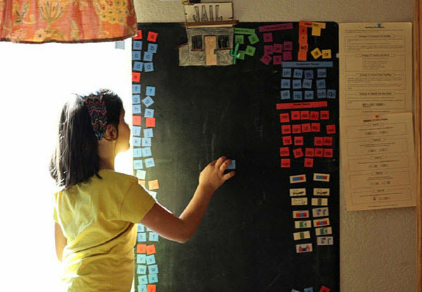 young girl works with letter tiles