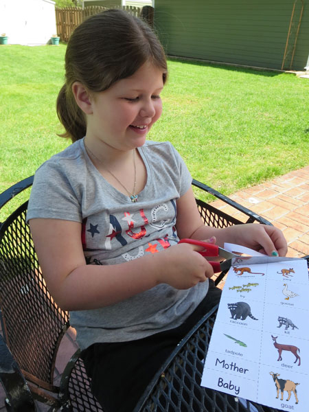 little girl cutting out baby animal name playing cards