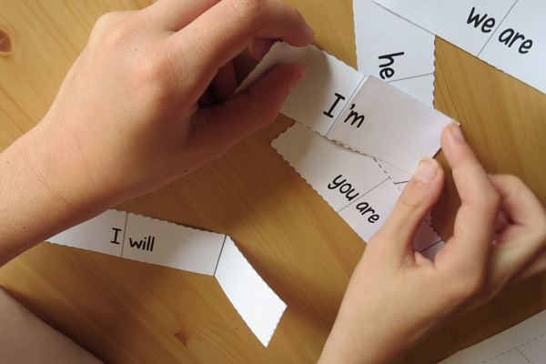Child folding paper to form the contraction 'I'm'