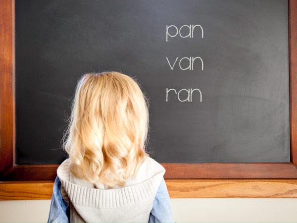 Young girl writing on chalkboard