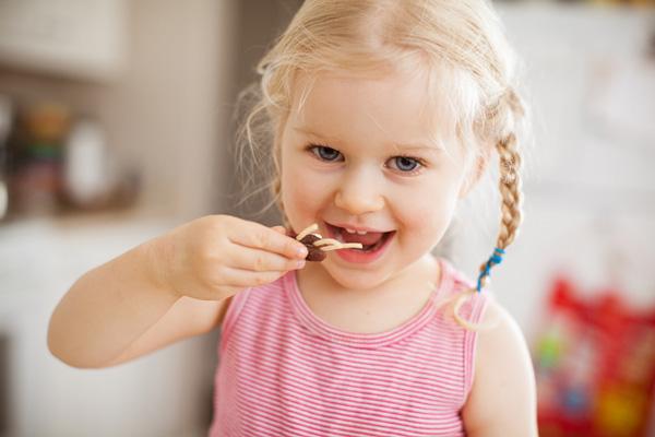 Happy preschooler eating snack