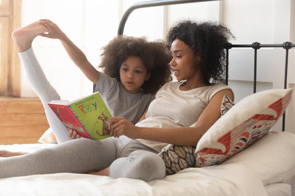 mom reading aloud to girl