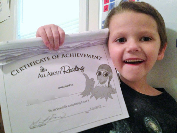 boy holds up aar completion certificate