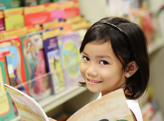 young girl reading a magazine