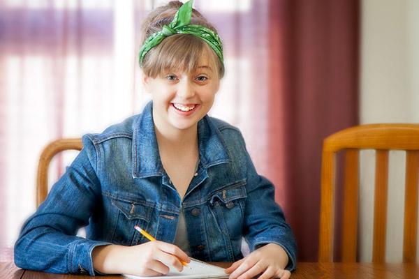 Smiling teenage girl writing on paper