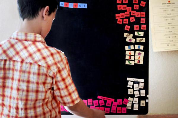 Teenage boy using letter tiles on board
