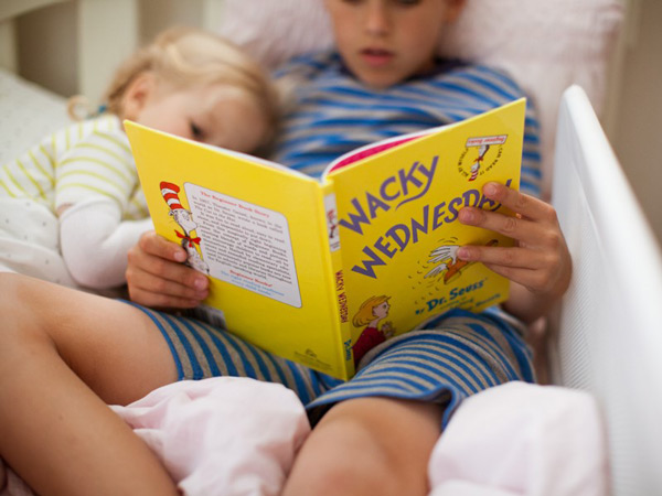 Boy reading to younger sister