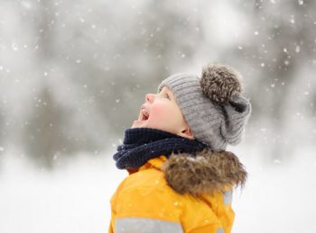 boy catching snowflakes on his tongue.