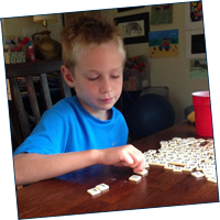 Boy spelling with letter tiles