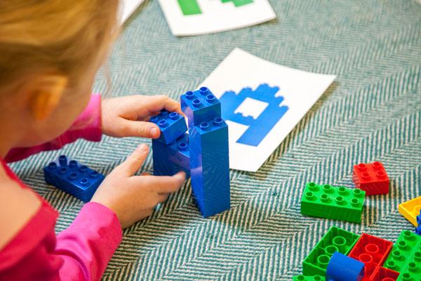 Preschooler building letter A with building blocks
