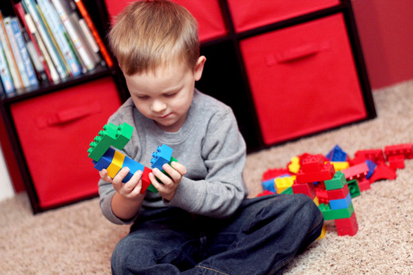 Preschooler building letter C with building blocks