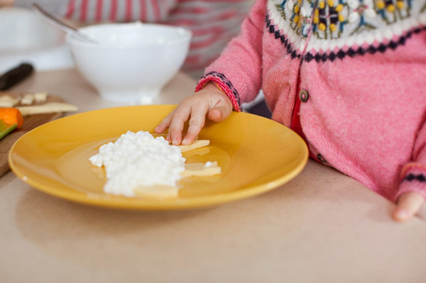 Child adding ingredients to plate