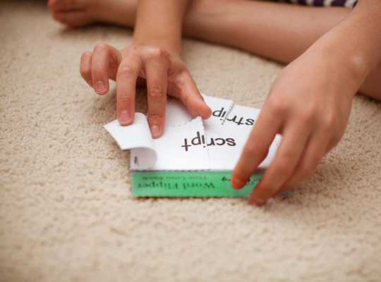 closeup of boy playing with a word flipper