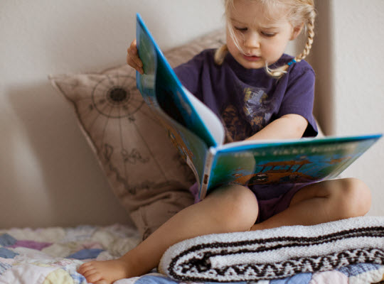 Young girl looking at book