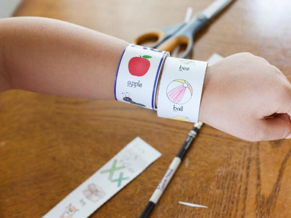 Child displaying ABC bracelets