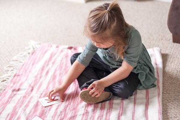Preschooler touching tactile letter card