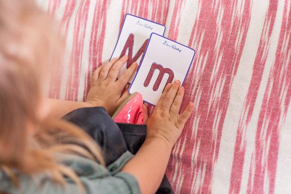 Preschooler matching tactile letter cards