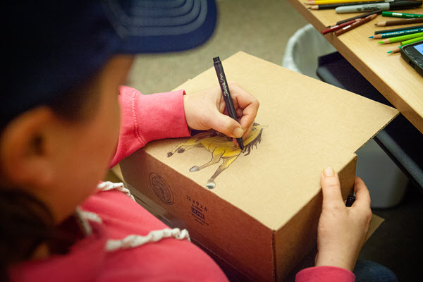 a woman drawing on a shipping box