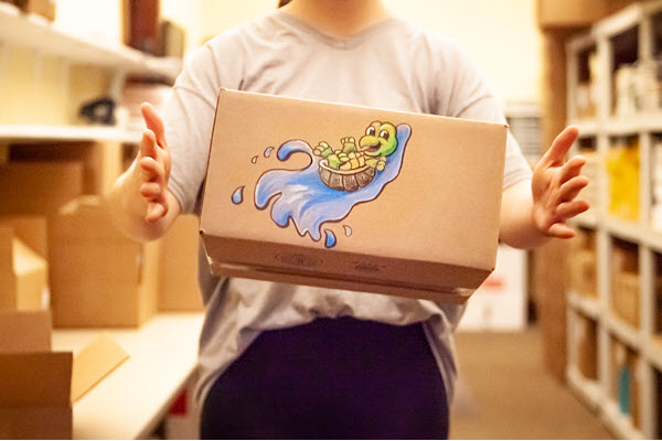 a shipping box with a turtle riding a wave