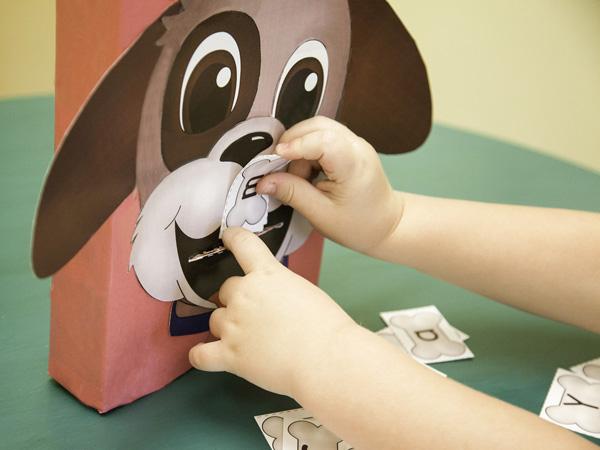 Preschooler feeding the puppy letters