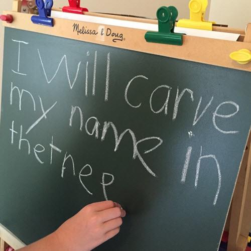 Child writing on chalkboard