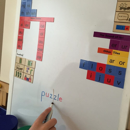 Child using All About Reading and All About Spelling on white board