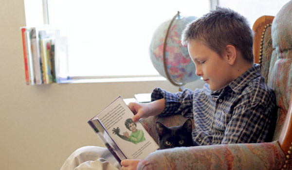 Boy in a chair reading independently.