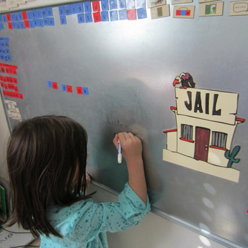 Image of child spelling a word with letter tiles.