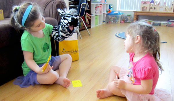 Older child teaching younger with Ziggy the zebra puppet.