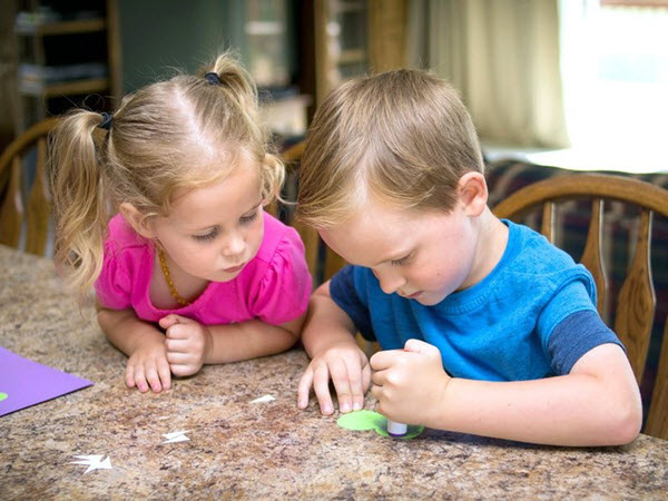 2 children gluing pieces for the letter A craft