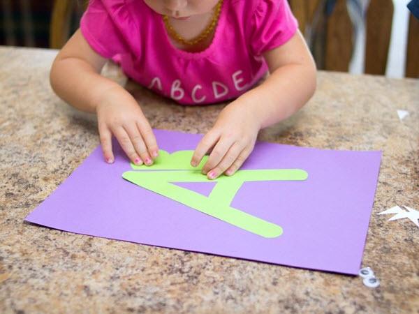 Little girl assembling her letter a craft