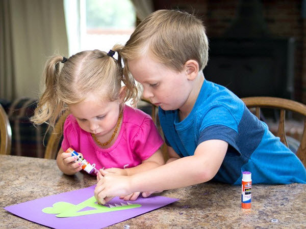 two children gluing teeth onto letter A alligator craft