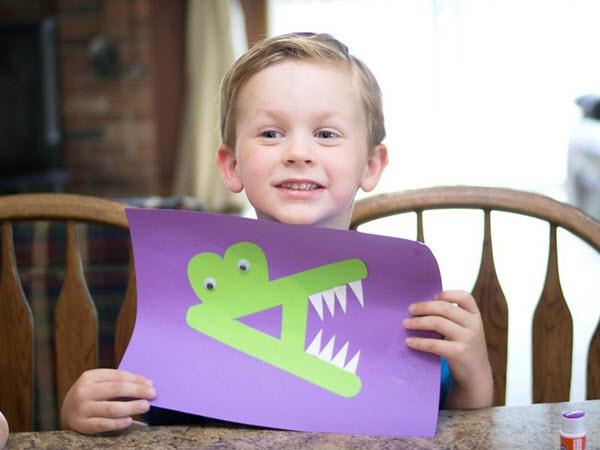 Little boy holding his finished letter A Alligator craft