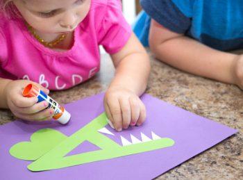 Little girl gluing teeth onto her alligator craft.