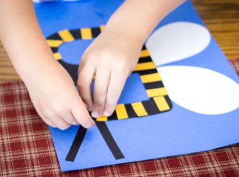 Child gluing eyes onto his bee craft.