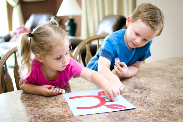 children applying eyes to letter c craft