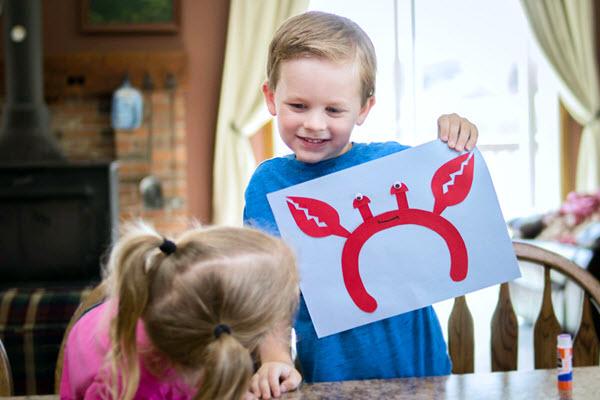 little boy holding up finished letter c craft