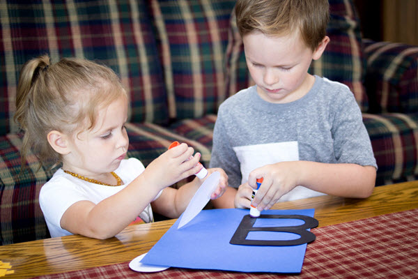 two children gluing together a bee craft